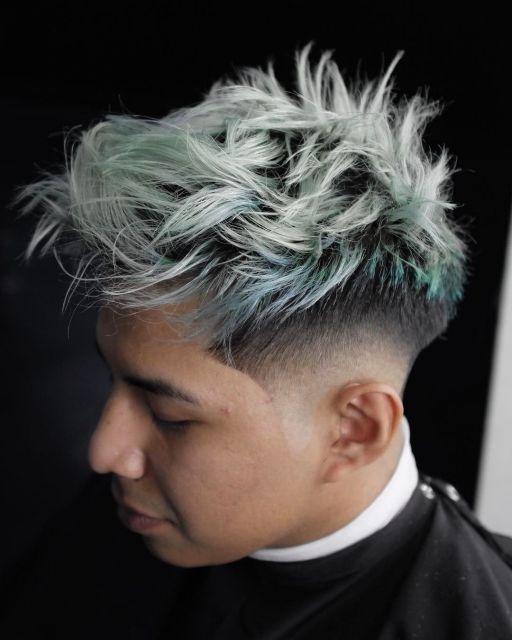 Homem no barbeiro de perfil. Seu cabelo é cortado em camadas com um pequeno degradê na lateral. Os fios do topo são platinados com azul.