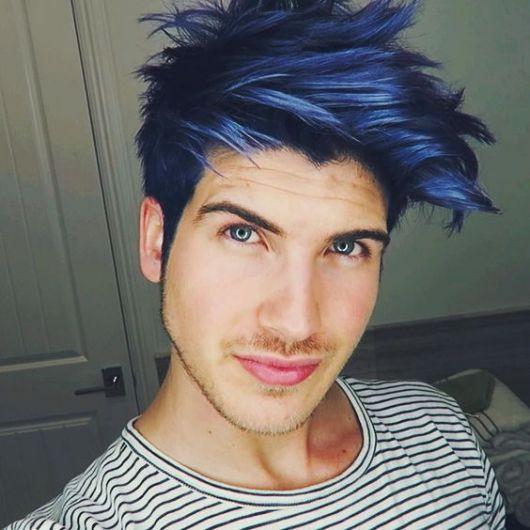 Homem tirando uma selfie. Ele tem um cabelo grande pintado com azul escuro e algumas luzes mais claras.