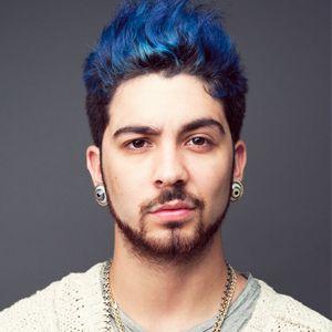 Homem olhando para a câmera. Ele usa dois alargadores, um em cada orelha, e uma corrente de metal. Seu cabelo é arrepiado para cima com os fios mais longos pintados de azul e a raiz com a cor natural.