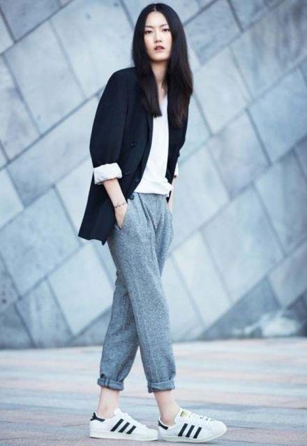 Modelo usa calça cinza de moletom, tenis branco e blazer.