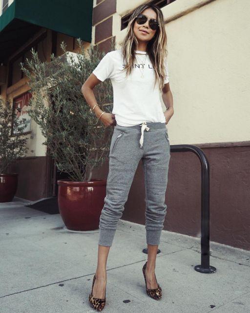 Modelo usa calça jogger cinza, scarpin preto e camiseta branca.