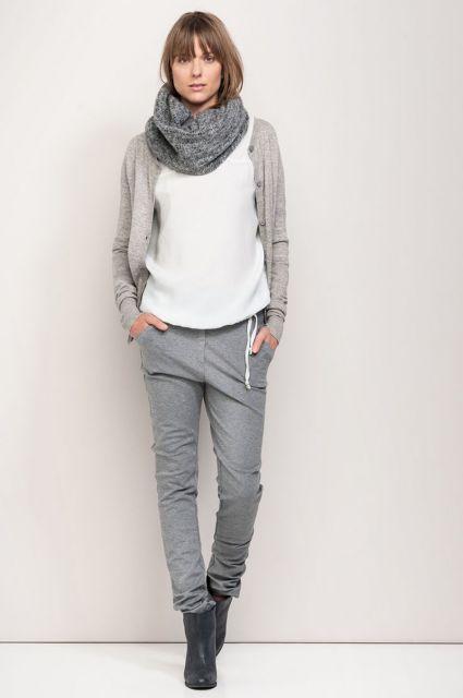 Modelo veste calça cinza jogger, camiseta branca, casaqueto cinza, sapato e cachecol.