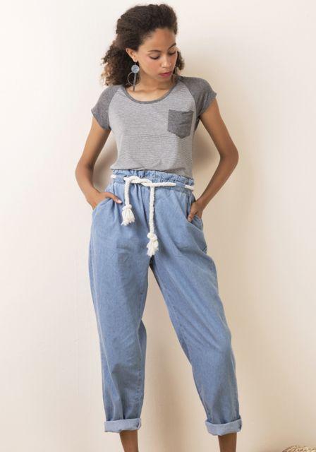 Modelo usa calça jeans azul claro, com camiseta cinza.