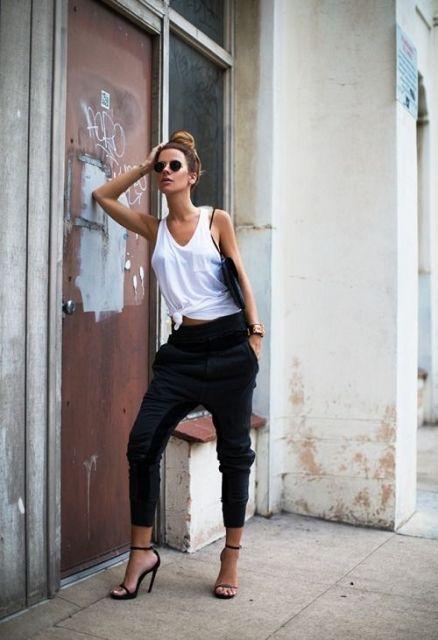 Modelo veste calça jogger preta com blusa regata branca com sandalia preta.