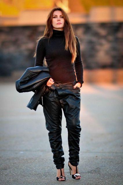 Modelo veste calça preta, blusa preta, jaqueta e sandalia na mesma cor.