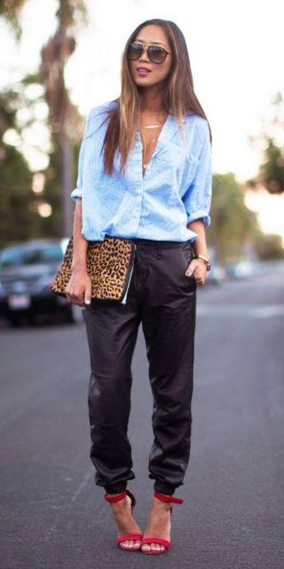 Modelo usa calça preta com camisa azul e sandalia vermelha.