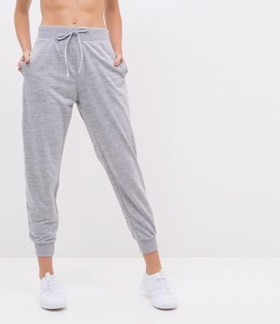 Modelo com calça jogger de moletom cinza e tenis branco.