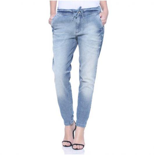 Calça jogger jeans combinada com blusa ranca e sandalia preta de tiras.