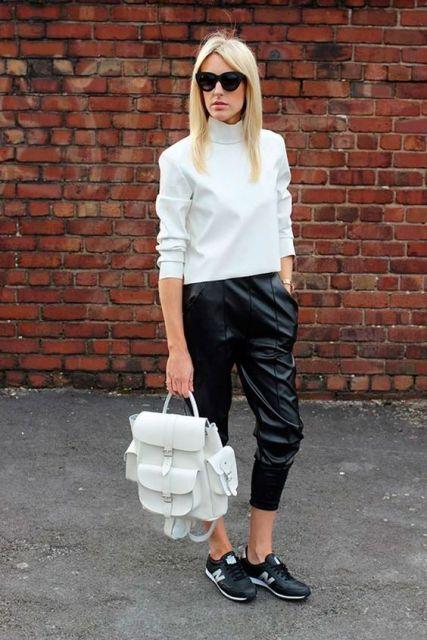 Modelo usa blusa branca, calça preta jogger e tenis.