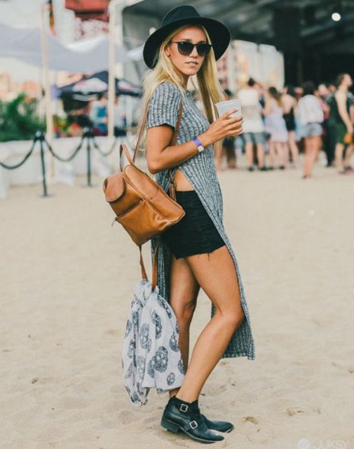 Modelo usa mochila marrom, saia, bota e camiseta longa com recorte lateral.