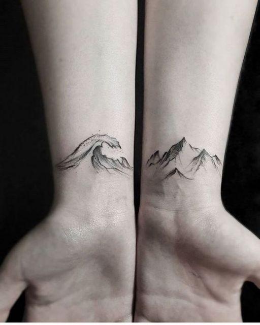 Duas tatuagens, uma em cada pulso. Em uma há o desenho de uma onda alta e no outro há diversas montanhas pontiagudas.