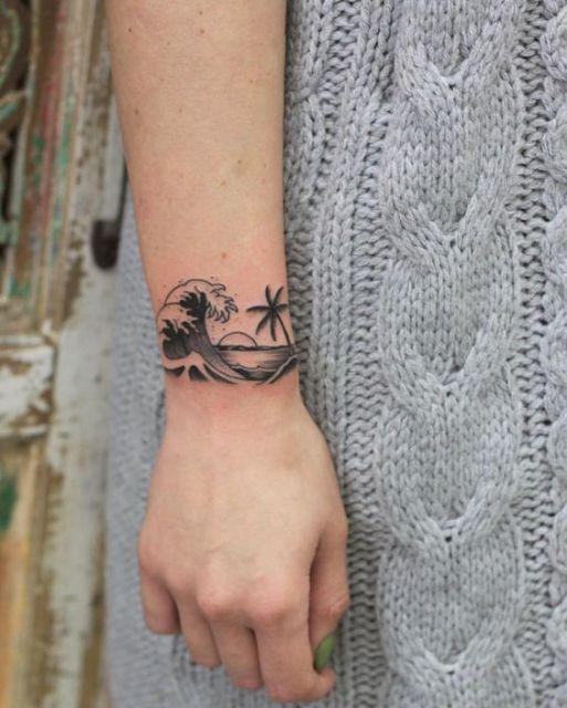 Tatuagem na parte externa do pulso com o desenho de uma onda se formando com o sol e um coqueiro a frente dela.