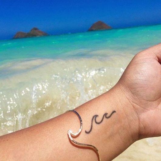 Tatuagem no pulso com o desenho de duas ondas formadas a partir de uma única linha.