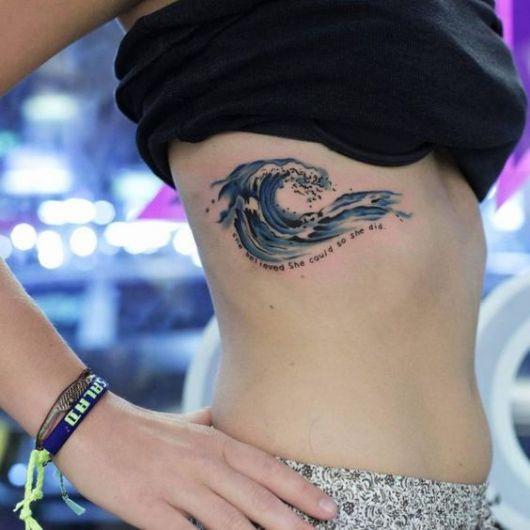 Mulher com a camiseta levantada para mostrar uma tatuagem de onda grande em sua costela. A tattoo é realista e colorida com o desenho de  uma onda prestes a quebrar.