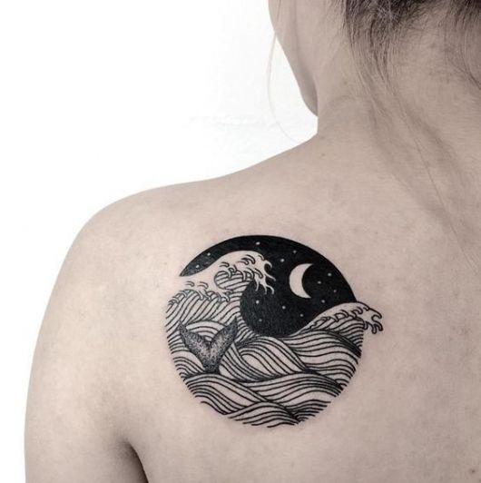 Tatuagem lateral nas costas de uma mulher. O desenho é de um círculo sem contorno com o interior preenchido com ondas no mar durante a noite e uma cauda de baleia entre elas.