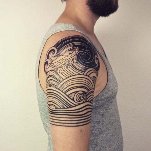 Tatuagem de onda na parte superior do braço de um homem. As ondas são formadas por diversas linhas sobrepostas que dão a impressão de um mar agitado.