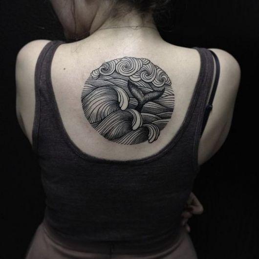 Tatuagem no centro das costas de uma mulher. O desenho é de um círculo sem contorno com ondas no mar, um céu nublado e uma cauda de sereia entre as ondas.