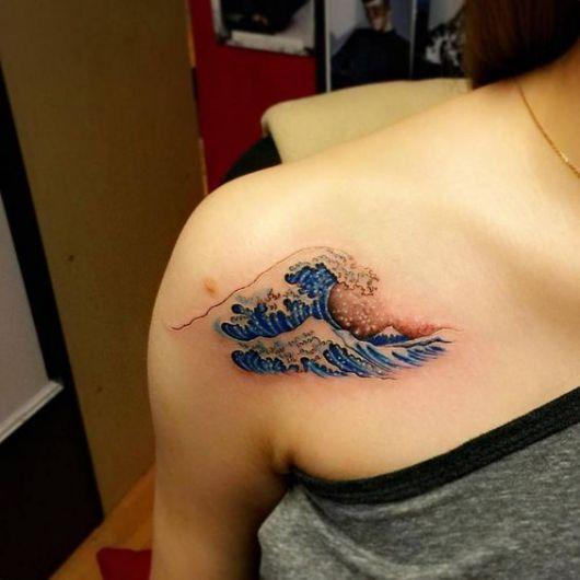 Tatuagem na parte frontal do ombro com o desenho de uma onda grande e colorida se formando no mar.