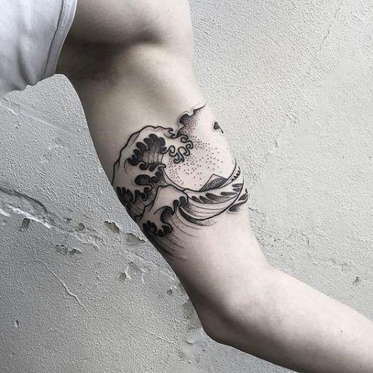 Tatuagem na parte interna do braço com o desenho de uma onda grande se formando.
