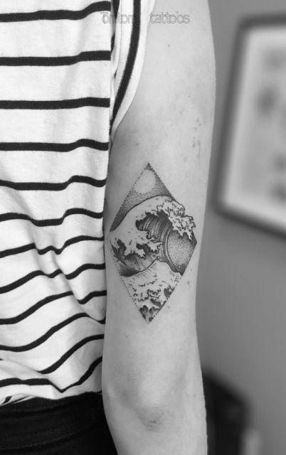 Tatuagem feita na parte de trás do braço com uma onda alta dentro de um losango.