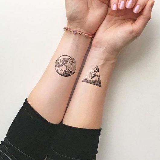 Duas tatuagens, uma em cada pulso. Em uma há o desenho de uma onda dentro de um círculo e na outra há o desenho de montanhas dentro de um triângulo.
