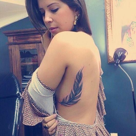Modelo com tatuagem de pena na lateral da costela.
