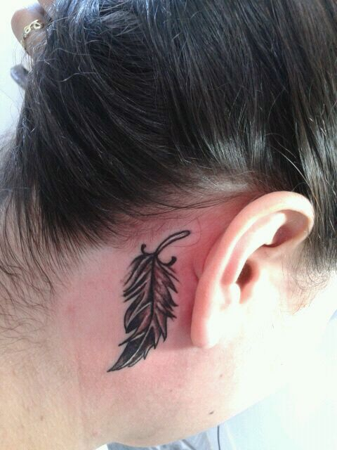 Tatuagem de pena pequena atrás da orelha de cabeça para baixo.