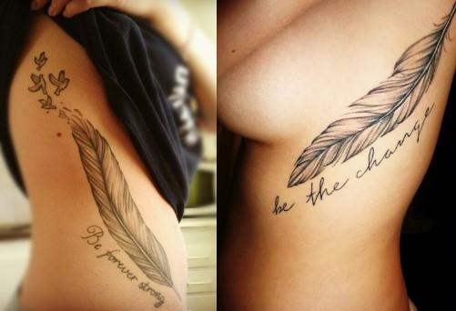 Duas tatuagens de pena grande com frases na costela.
