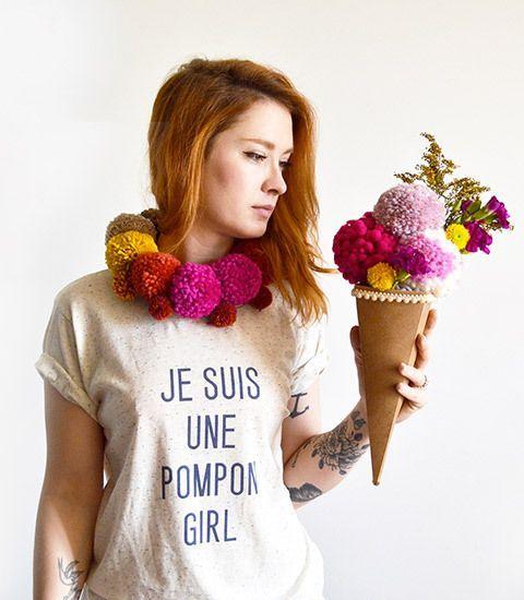 Mulher com camiseta com frase e cachecol de pompom.