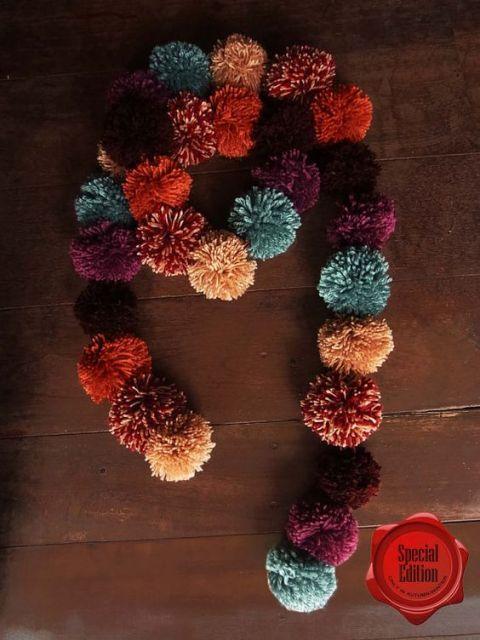 Cachecol de pompom com as cores azul, vermelho, bege e roxo.