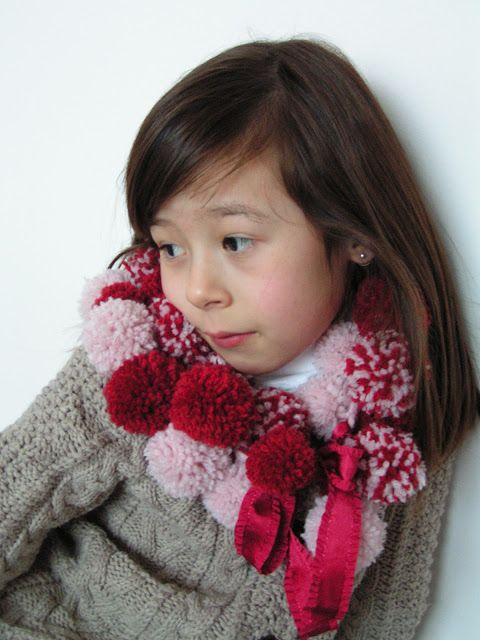 Criança com cachecol de pompom.