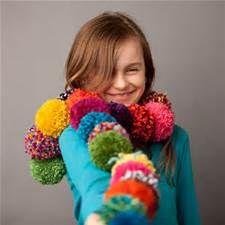 Criança usando blusa azul e cachecol de pompom.