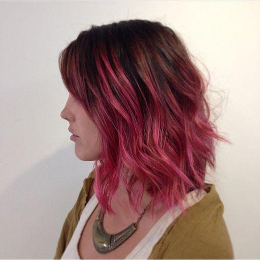 Mulher de perfil, com cabelo com Ombré Hair e mechas rosas.