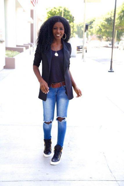 Modelo usa calça jeans rasgada no joelho, blusa preta, blazer e tenis.