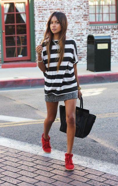 Modelo usa tenis vermelho cano alto, saia e blusa listrada em preto e branco.
