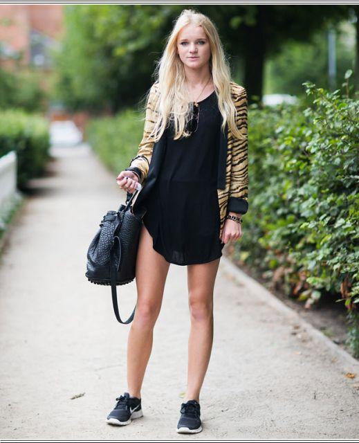 Modelo veste vestido preto, tenis preto e jaqueta de estampa de oncinha.