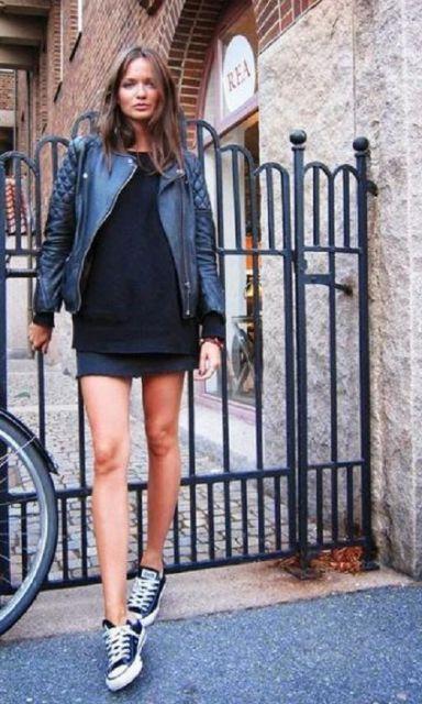Modelo usa saia preta, blusa preta, jaqueta e tenis all star.