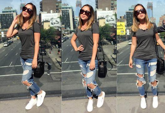 Modelo usa calça destruída jeans, camisetinha podrinha, bolsa preta e tenis branco.