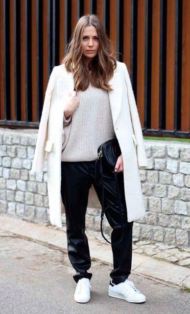 Modelo usa calça preta, tenis branco e casaco branco longo.