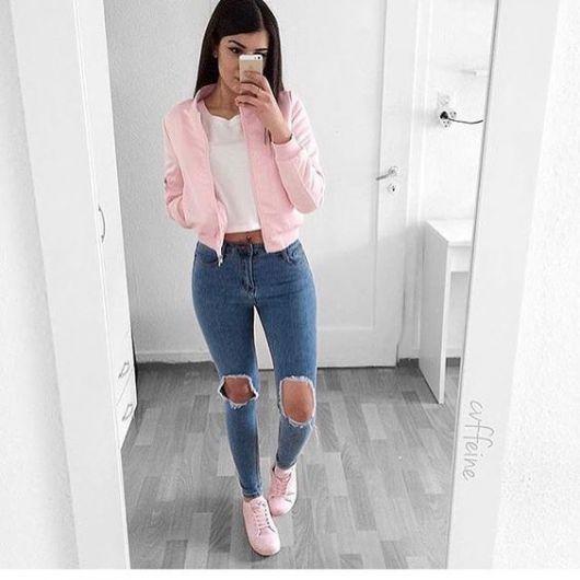 Modelo usa jeans, camiseta branca, jaqueta e tenis cor de rosa.