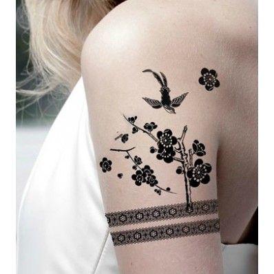 Tatuagem bracelete feminino acompanhada de flores e pássaro.