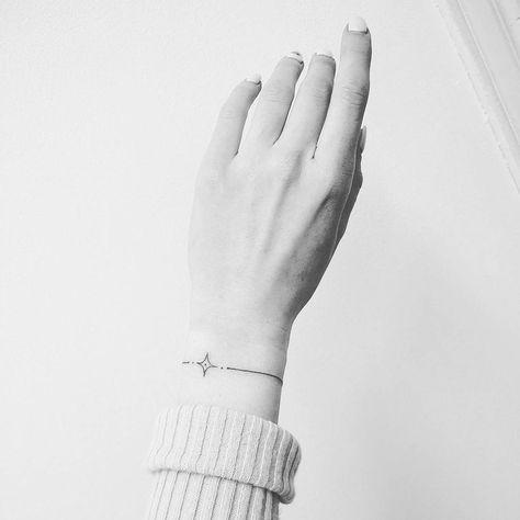 Tatuagem fina próxima ao pulso.