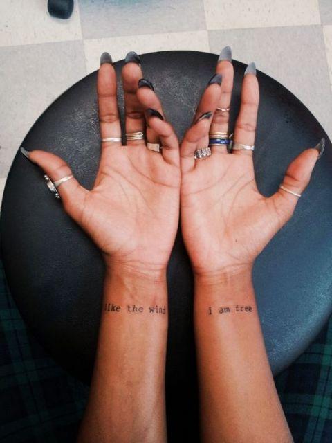 Mulher com tatuagem nos dois pulsos e com vários anéis.