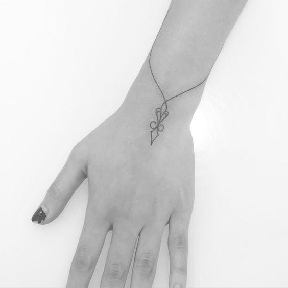 Tatuagem que se assemelha a uma pulseira com pingente.