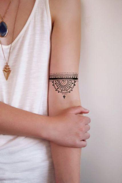 Mulher com regata branca e tatuagem no braço.