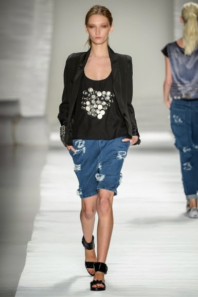 Modelo veste bermuda jeans com blusinha preta, blazer e tenis