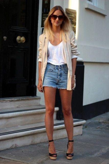 Modelo veste bermuda jeans curta, blusa branca, sandalia de salto anabela e casaqueto nude.