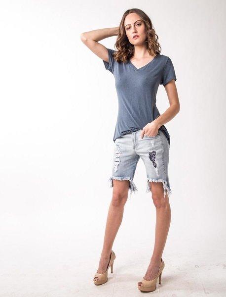 Modelo veste bermuda jeans, camiseta cinza e sandália.