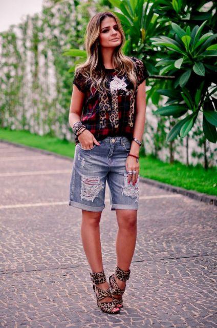 Modelo usa bermuda jeans com sandalia preta e blusinha estampada na mesma cor.