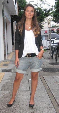 Modelo usa bermuda jeans cinza com sapatilha preta, blusa branca e blazer pretinho.